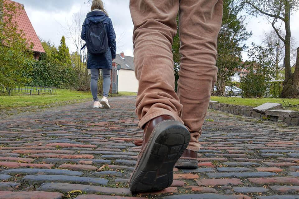 2 Personen laufen auf einer Pflasterstraße - Sinnbild für Mobile Jugendarbeit